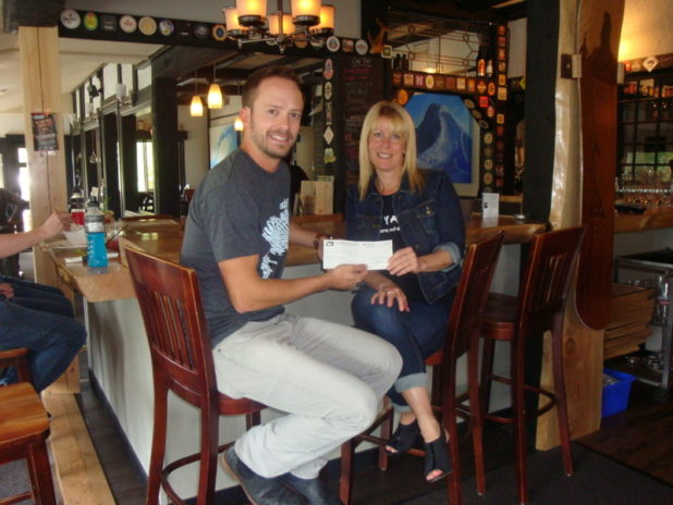 Robin from the White Whale presenting a cheque for $750.00 to Ocean from YANA